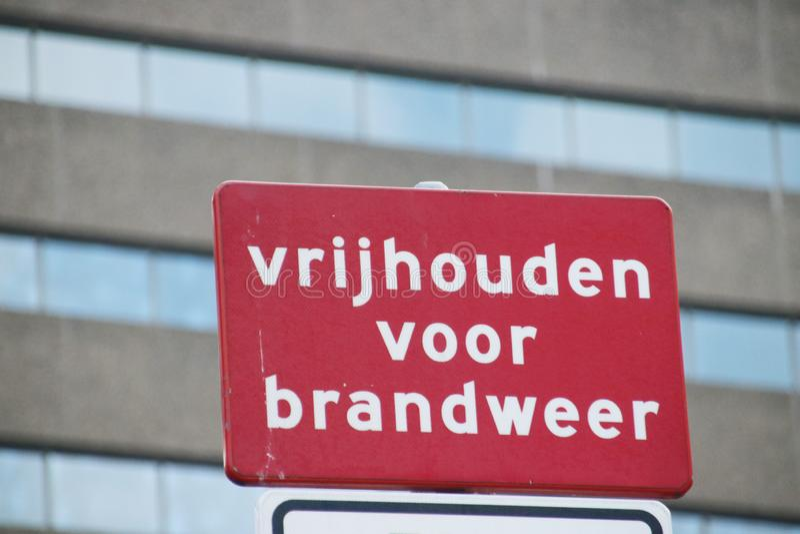 Rode sigh met witte brieven ervoor waarschuwen die dat de uitgang voor de brandbrigade in Den Haag, Nederland duidelijk moet blij royalty-vrije stock afbeelding