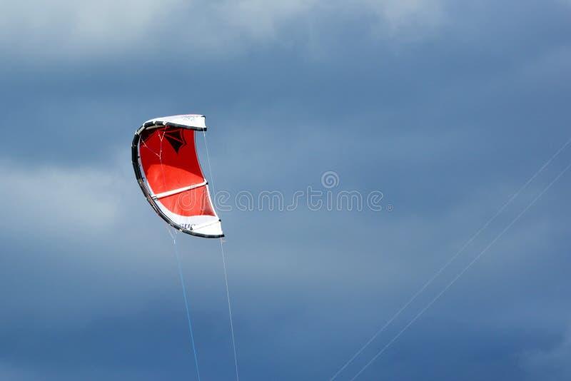 Rode sleevlieger die voor bewolkte hemel vliegen royalty-vrije stock afbeeldingen