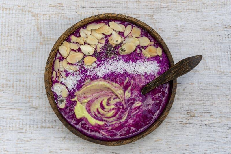 Rode smoothie in kokosnotenkom met draakfruit, avocado, amandelvlokken, kokosnotenspaanders en chiazaden voor ontbijt, sluit omho royalty-vrije stock afbeelding