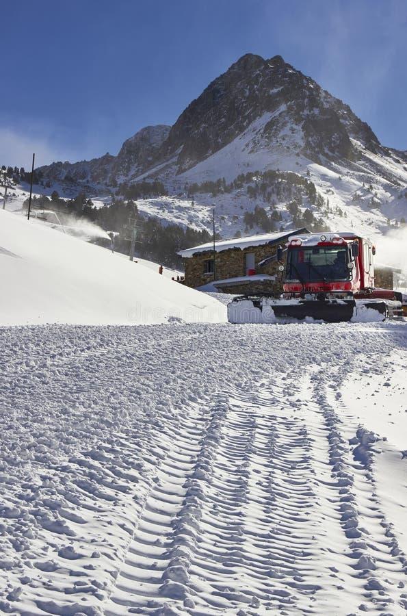 Rode sneeuw groomer in de berg stock afbeelding