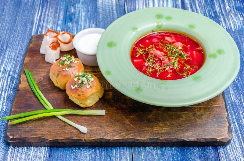 Rode soep in een groene plaat, broodjes, bacon, uien en saus stock foto's