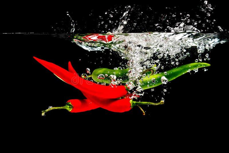Rode Spaanse pepers in water stock fotografie