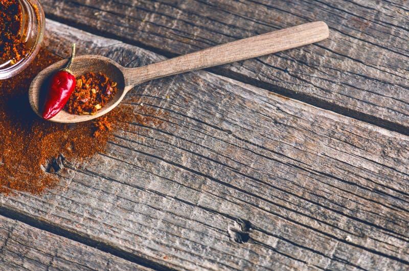 Rode Spaanse peperspeper, kruidig op een houten lepel Groente op een donkere, houten lijst Concept heet voedsel royalty-vrije stock afbeelding
