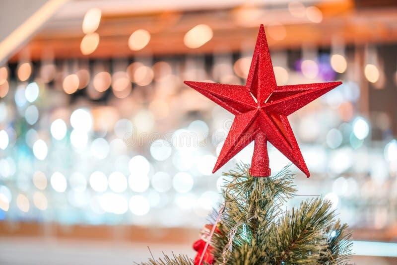 Rode sterdecoratie op drie met behide van de onduidelijk beeld grote Kerstboom royalty-vrije stock foto's