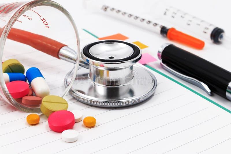 Rode stethoscoop, spuiten, pen, en vele kleurrijke pillen op lege blocnote stock foto's