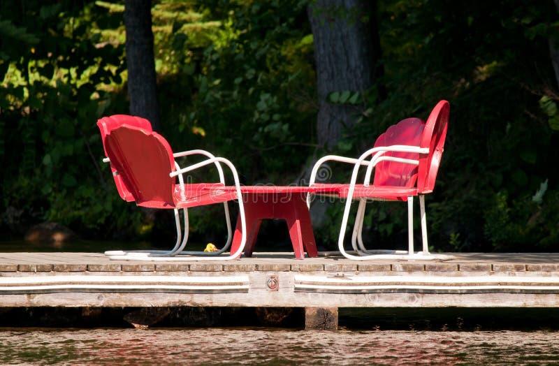Rode stoelen op een dok stock fotografie