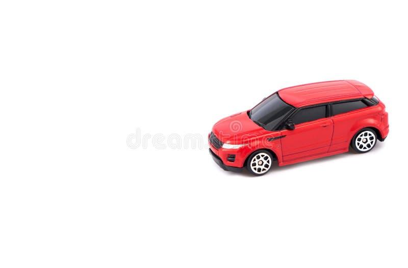 Rode stuk speelgoed auto op witte achtergrond stock fotografie