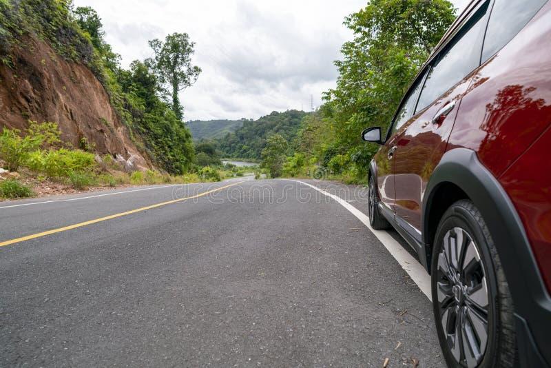 Rode Suv-auto op Asfaltweg met berg groen bosvervoer om concept te reizen royalty-vrije stock foto's
