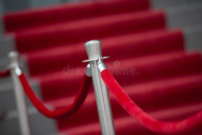 Rode tapijt en barrièrekabel stock foto's