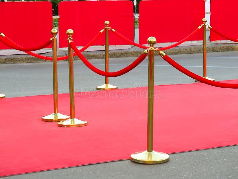 rode tapijtingang met gouden stangen en kabels Beroemdheidsbenoemden aan première Sterren op het feestelijke toekennen van prijze stock afbeeldingen