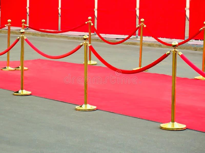 rode tapijtingang met gouden stangen en kabels Beroemdheidsbenoemden aan première Sterren op het feestelijke toekennen van prijze royalty-vrije stock fotografie
