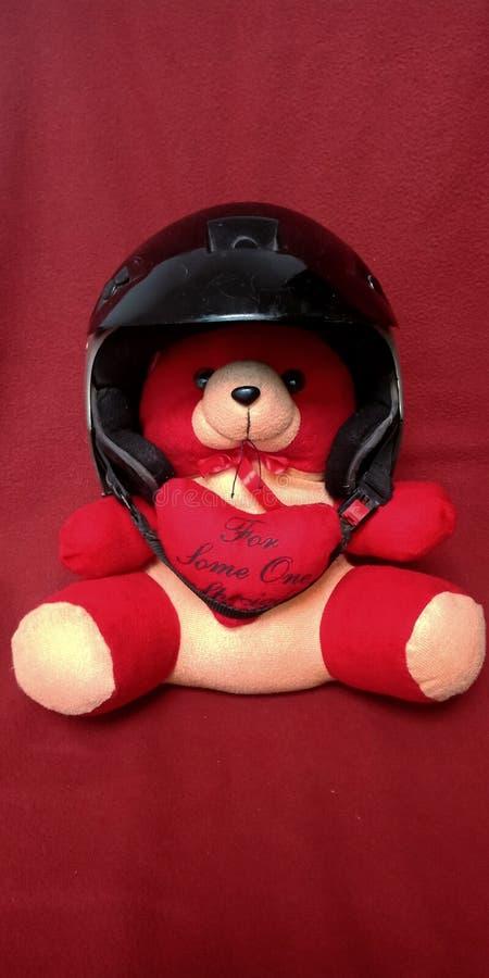 Rode teddybeer dragende helm in rode achtergrondvoorraadfoto stock fotografie