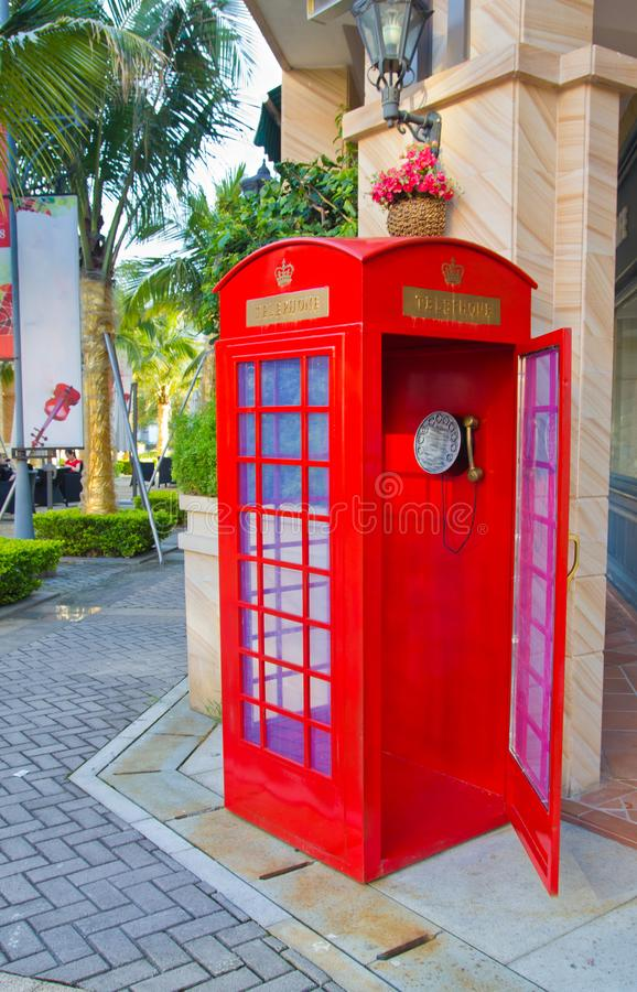 Rode telefooncel met een open deur op een de zomer zonnige straat stock afbeeldingen