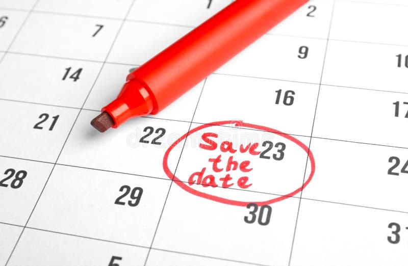 """Rode teller en uitdrukking \ """"sparen de Datum \"""" die op kalender, close-up wordt geschreven stock fotografie"""