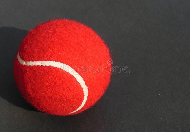 Rode Tennisbal met witte krommelijn op donkere grijze achtergrond royalty-vrije stock afbeelding