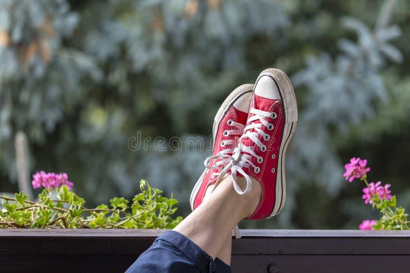 Rode tennisschoenen op de benen van een meisjestiener tegen de achtergrond van aard stock foto's