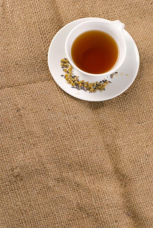 Rode thee in ceramische kop met juteachtergrond stock foto's