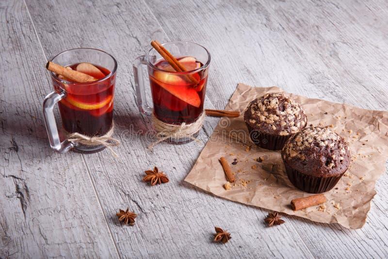 Rode theekoppen en chocolade cupcakes op een lijstachtergrond Citroenthee met koekjes De winterontbijt stock afbeelding