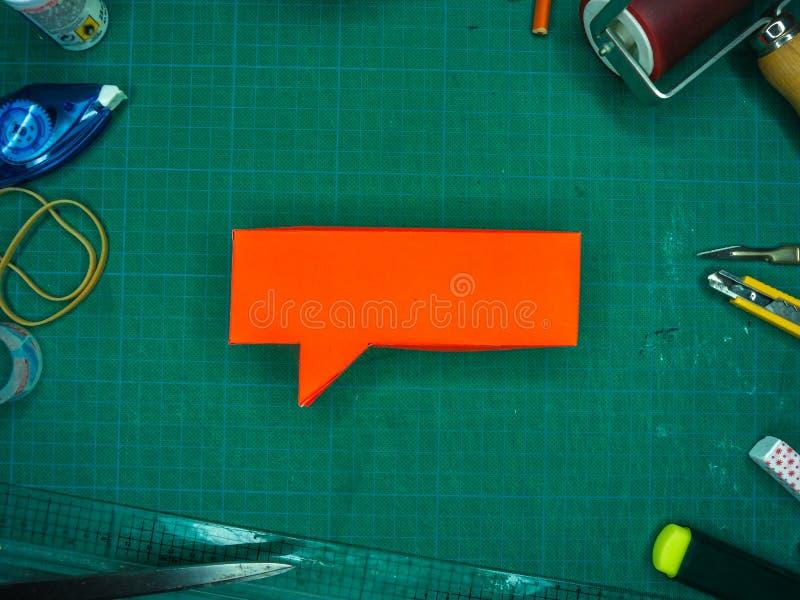 Rode Toespraakbel op Groene Scherpe Mat, met diverse hulpmiddelen, schot stock fotografie