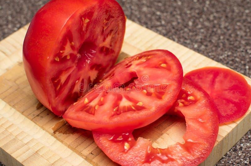 Rode tomaat op houten scherpe raad in plakken royalty-vrije stock afbeelding