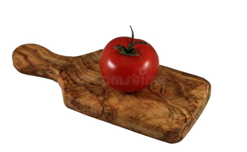 Rode tomaat op olijf houten scherpe raad stock fotografie
