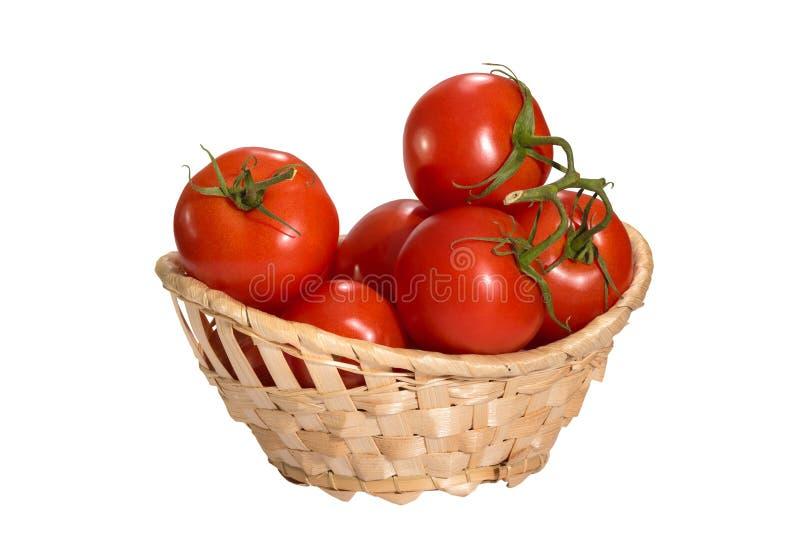 Rode tomaten in een mand op de wit geïsoleerde achtergrond stock foto
