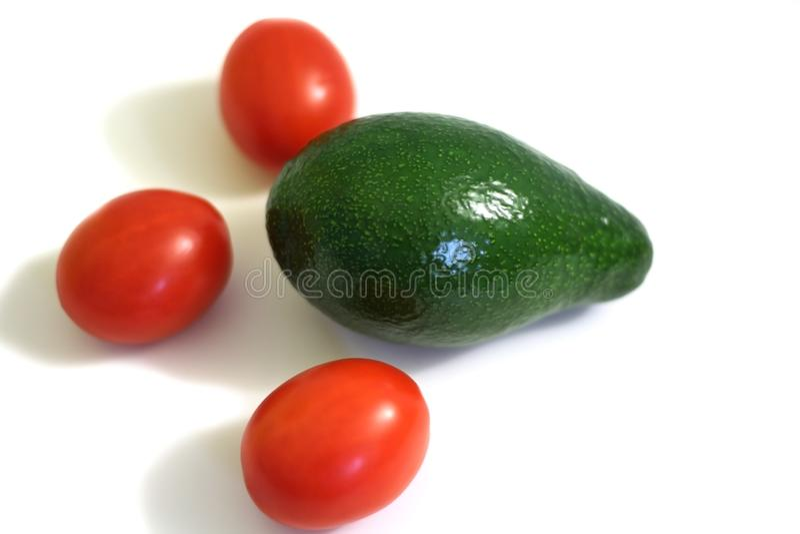 Rode tomaten en groene avocado op witte achtergrond stock fotografie