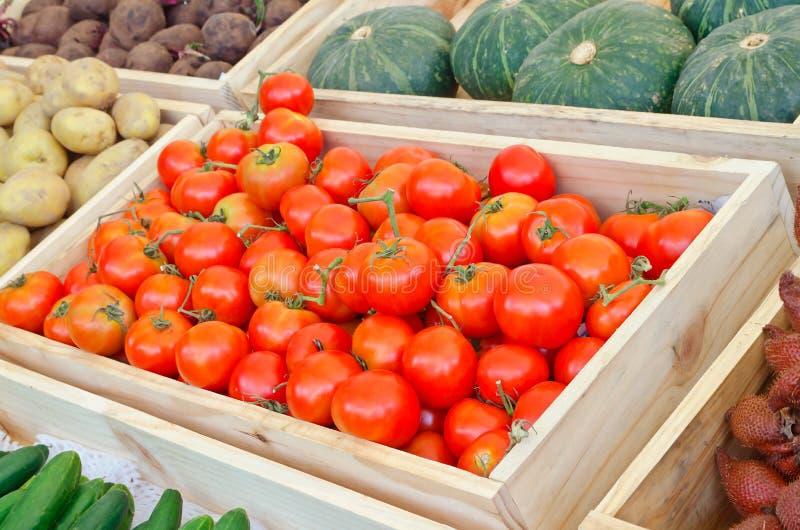 Rode tomaten en groente bij landbouwersmarkt royalty-vrije stock afbeeldingen