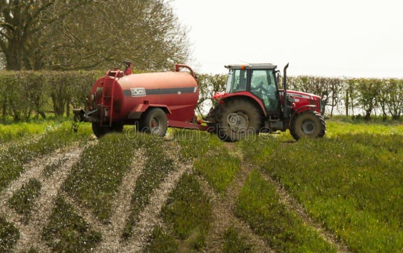 Rode tractor het uitspreiden het uitspreiden dunne modder op gebieden stock foto's