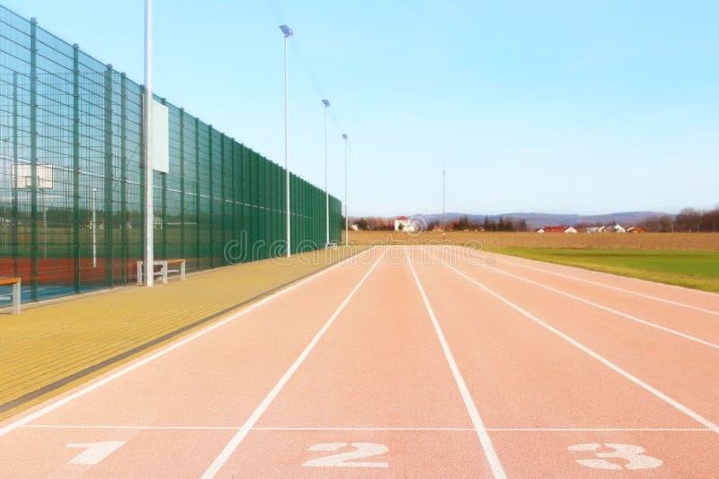 Rode tredmolen bij het stadion Element van complexe sporten Openluchtdeklaag voor sporten Een plaats voor competities in atletiek stock afbeeldingen