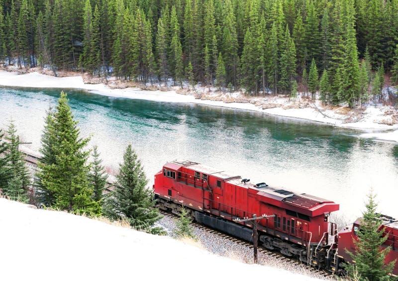 Rode trein die langs spoorwegspoor door de winter bosw reizen stock afbeelding