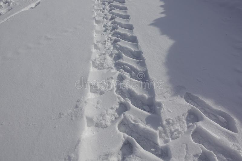 Rode trilhas na neve, trator das pegadas do detalhe Pegadas do trator na neve em um dia ensolarado foto de stock
