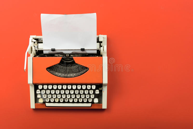 Rode uitstekende schrijfmachine met wit leeg document blad royalty-vrije stock afbeelding