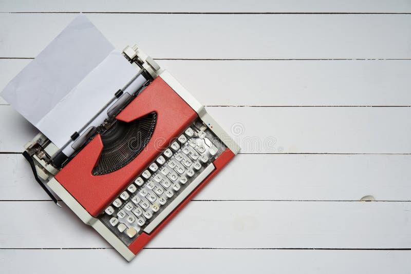 Rode uitstekende schrijfmachine met wit leeg document blad op witte houten lijst royalty-vrije stock afbeeldingen