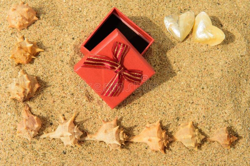 Rode vakje gift op zandig strand met shells, achtergrond met exemplaarca stock afbeeldingen