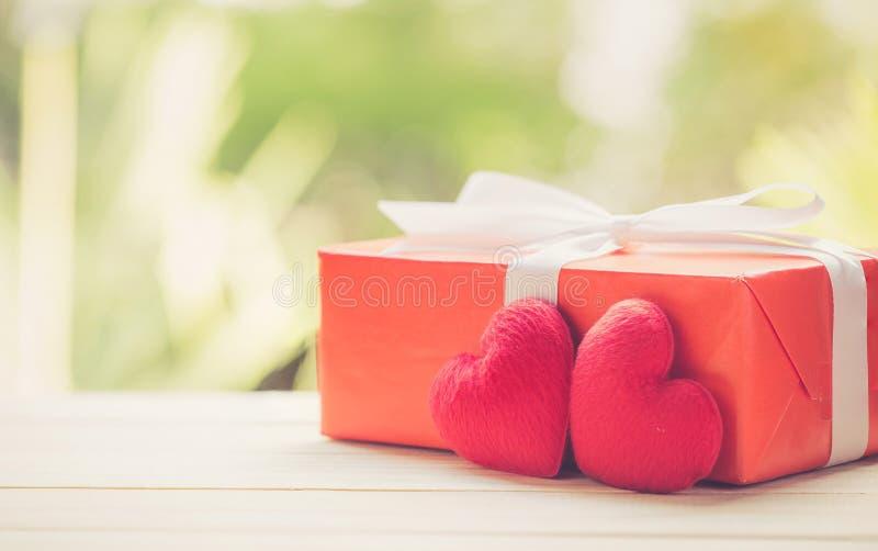 Rode van het giftvakje en hart vorm op houten lijstbovenkant met achtergrond van het aard de groene onduidelijke beeld bokeh royalty-vrije stock afbeelding