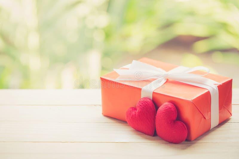 Rode van het giftvakje en hart vorm op houten lijstbovenkant met achtergrond van het aard de groene onduidelijke beeld bokeh stock fotografie