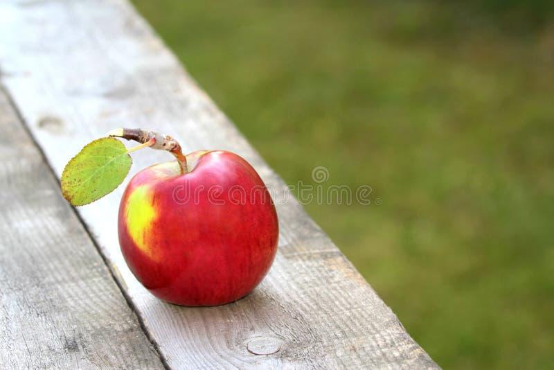 Rode, verse en organische appel op oude lijst stock afbeeldingen