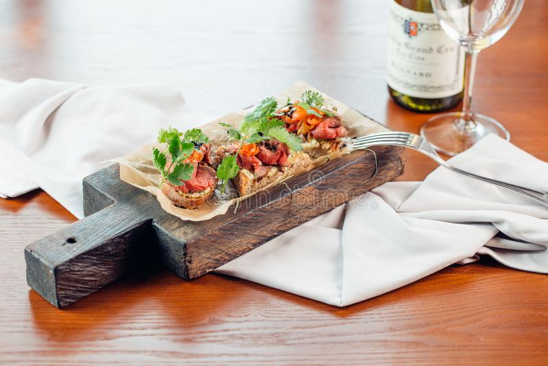 Rode vissen en arugulasandwich op een raad, selectieve nadruk stock fotografie