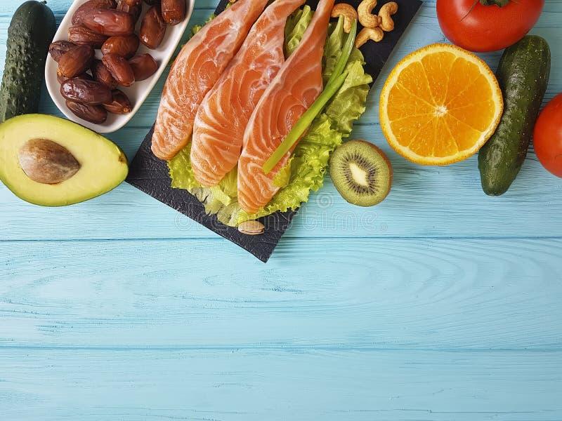 Rode vissen Omega 3, vers de notenassortiment van het avocadodiner op blauwe houten, samenstellings gezond voedsel stock foto