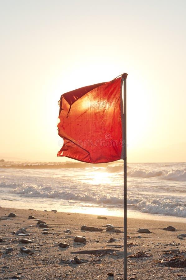 Rode vlag op het strand stock afbeeldingen