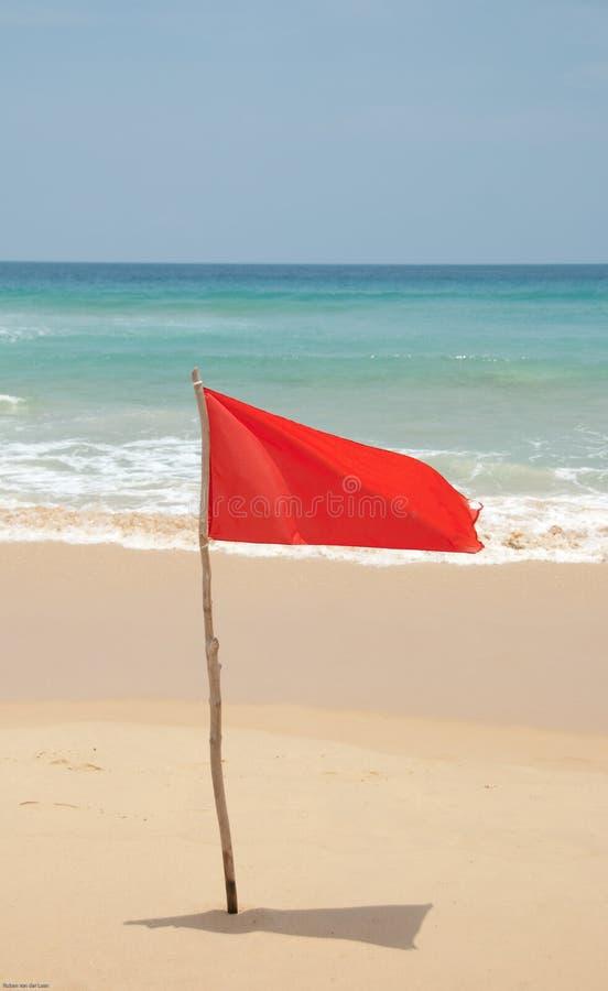 Rode vlag op strand stock foto