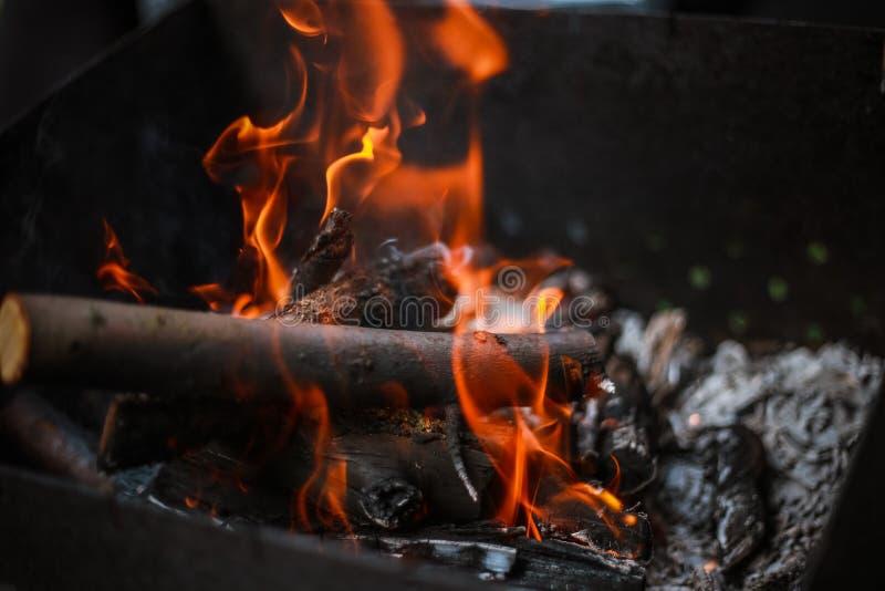 Rode vlam van een besnoeiing van een boom, donkergrijze steenkolen binnen een metaalkoperslager Brandhout het branden in een kope stock fotografie