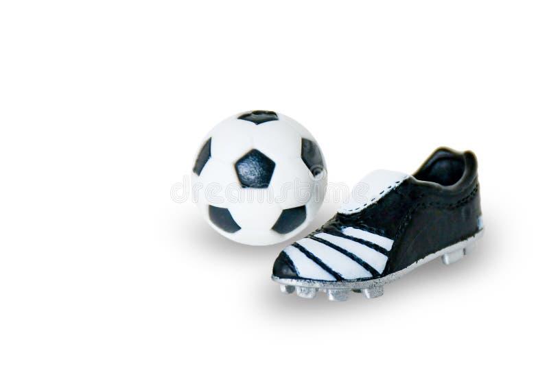 Rode Voetbalbal met schoenen op witte achtergrond met het cliping van weg royalty-vrije stock afbeelding