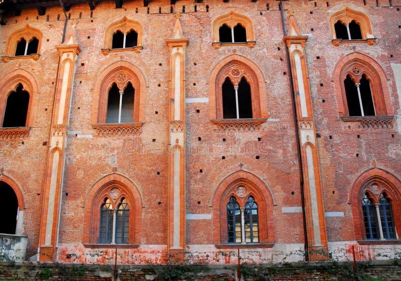 Rode voorgevel met negen prachtige vensters met verticale raamstijlen in het kasteel van Vigevano dichtbij Pavia in Lombardije (I royalty-vrije stock fotografie