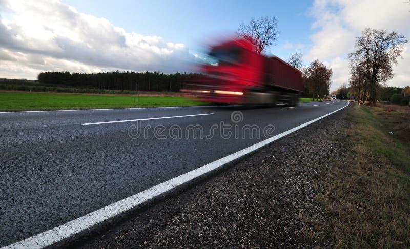 Rode vrachtwagen in een motie op tarmacweg stock fotografie