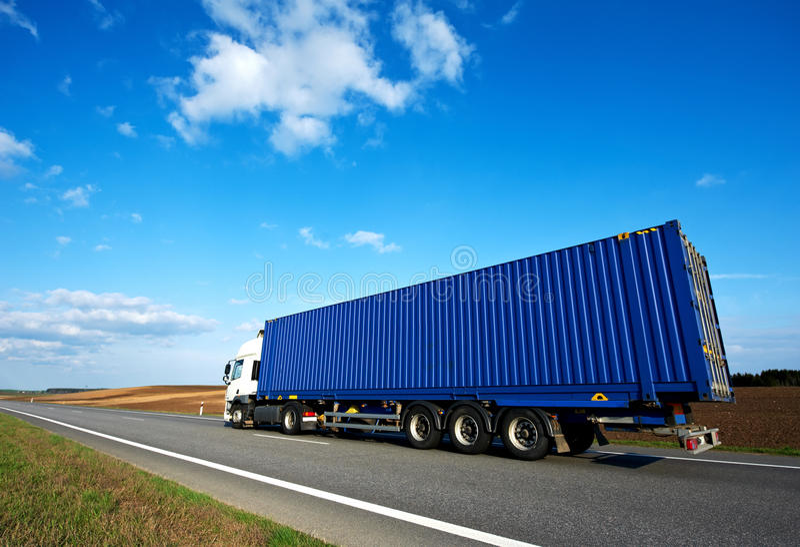 Rode vrachtwagen met grijze aanhangwagen over blauwe hemel royalty-vrije stock foto