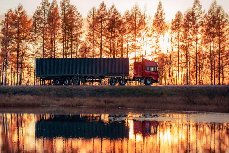 Rode vrachtwagen op een weg bij zonsondergang stock afbeelding