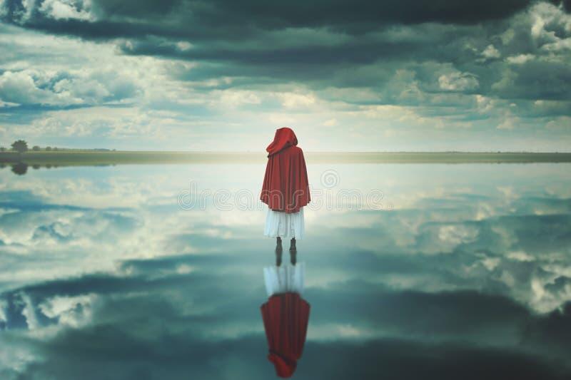Rode vrouw met een kap in een vreemd landschap met wolken stock afbeeldingen
