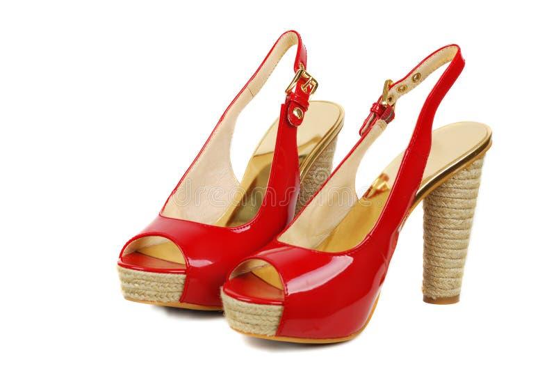Rode vrouwenschoenen die op witte achtergrond worden geïsoleerda royalty-vrije stock afbeeldingen